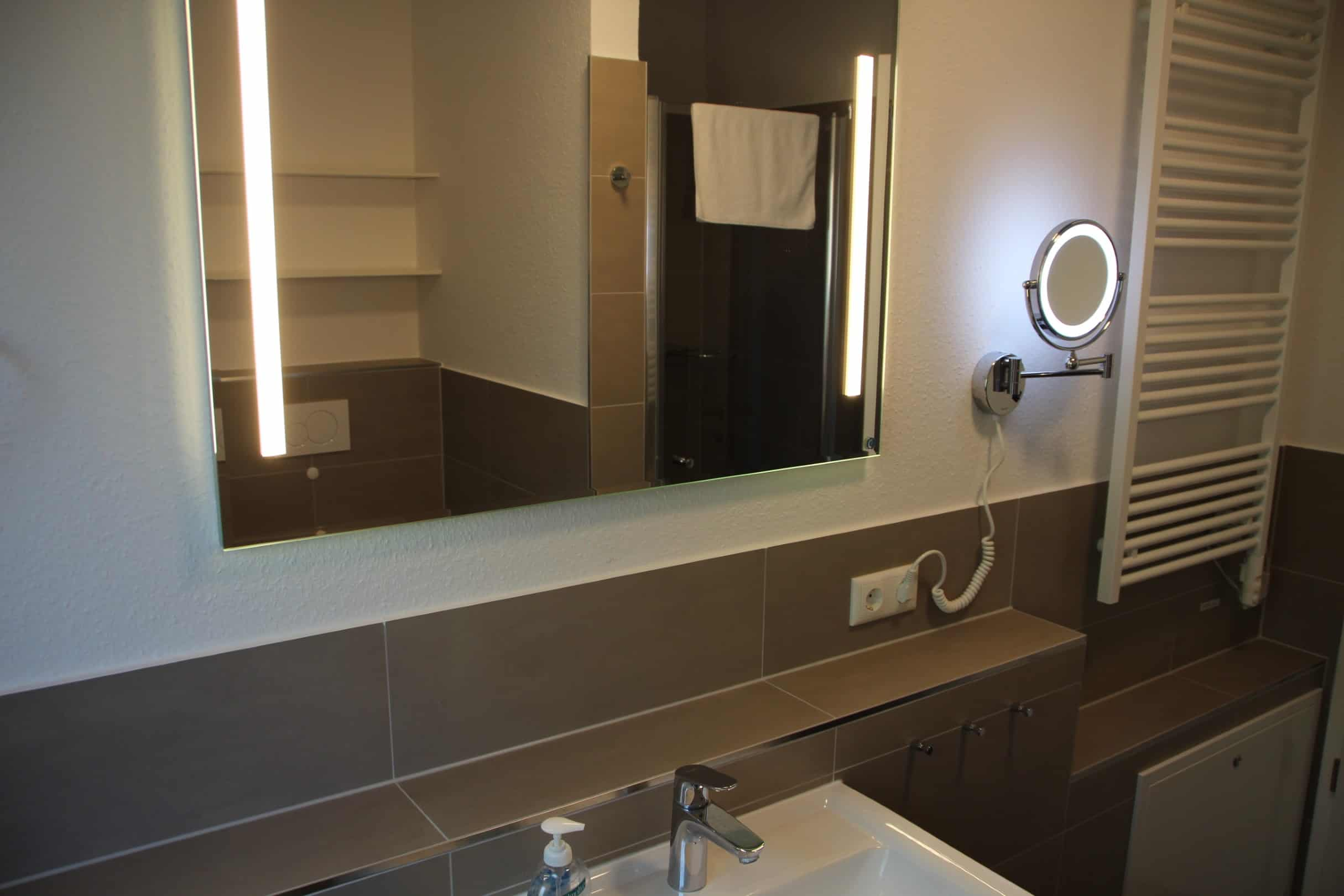 Badezimmer mit Handtuchwärmer und Kosmetikspiegel